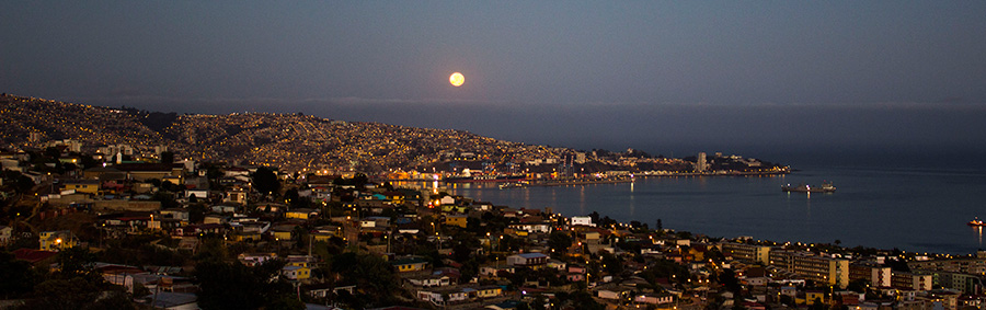 """MEJOR FOTOGRAFÍA SECTOR CENTRO   Título: """"Bajadas Porteñas"""".   Autor: Rodrigo Vidal. Descripción: Todo desciende al mar, los cerros, las calles, personas, el agua de la lluvia y la Luna, en este caso, por detrás de Playa Ancha. Foto tomada desde Viña Del Mar, Región de Valparaíso, centro de Chile."""