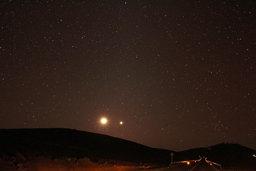 """MENCIÓN HONROSA 4   Título: """"Luna Binaria"""".  Autor: Nils Reichhard. Descripción: Foto tomada en una noche camino al Observatorio Paranal, visible al lado derecho sobre el cerro, mientras la Luna y Venus comparten el horizonte. Cerro Paranal, Región de Antofagasta, norte de Chile."""