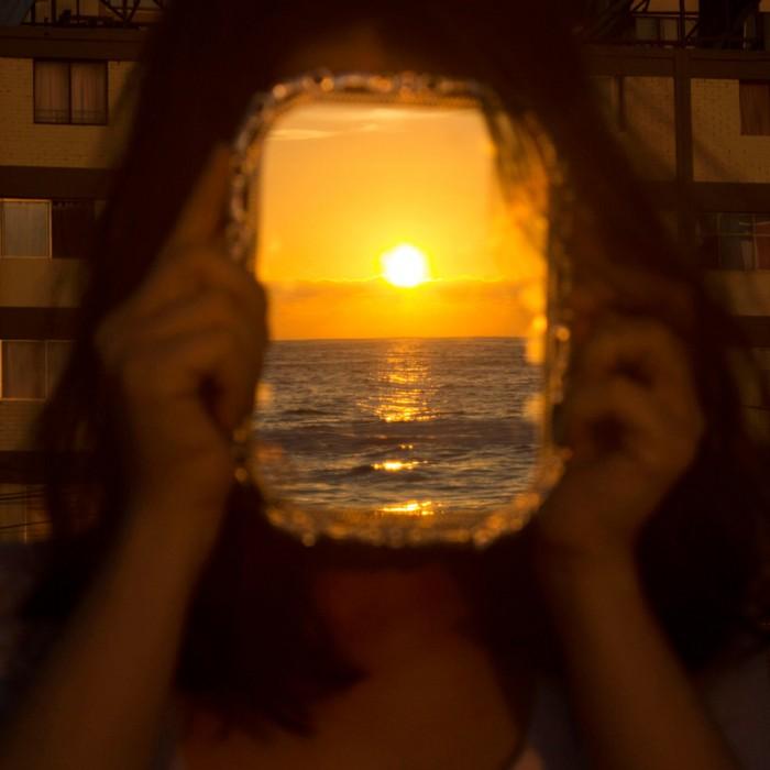 """Mejor foto zona norte: """"Con el Sol en la cara"""".  Autora: Mariana Garrido; Antofagasta.  """"Sentada sobre unas rocas en el borde costero y frente al mar en plena puesta de Sol antofagastina, la cual es reflejada en un espejo"""". Foto tomada en marzo 2016; región de Antofagasta."""