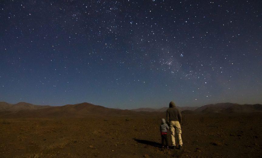 """Mención honrosa 5: """"Mostrando el hogar"""".  Autor: Rodrigo Escuti.  """"Junto a mi nieto, gran compañero y aprendiz en las noches de observación. Esa noche buscábamos observar el cometa Lovejoy. Se aprecia la Vía Láctea, el Saco de Carbón y la Cruz del Sur"""". Foto tomada en diciembre 2014; región de Atacama."""