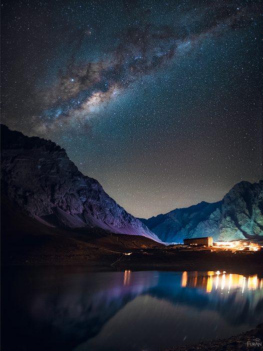 """""""Ski and the Skies""""Mejor Foto Zona Centro""""La Laguna del Inca tiene orillas peligrosas, adentrarse a recorrerla en la noche es un tramo complejo, pero luego de caminar algunos minutos la vista es el merecido premio. El Hotel Portillo se alza entre las montañas, mientras millones de estrellas en el firmamento lo ven, inmóvil bajo la noche"""". Portillo, RM.Autor: Exequiel Pérez; Pudahuel.Premio: Telescopio Celestron Astromaster 70AZ"""