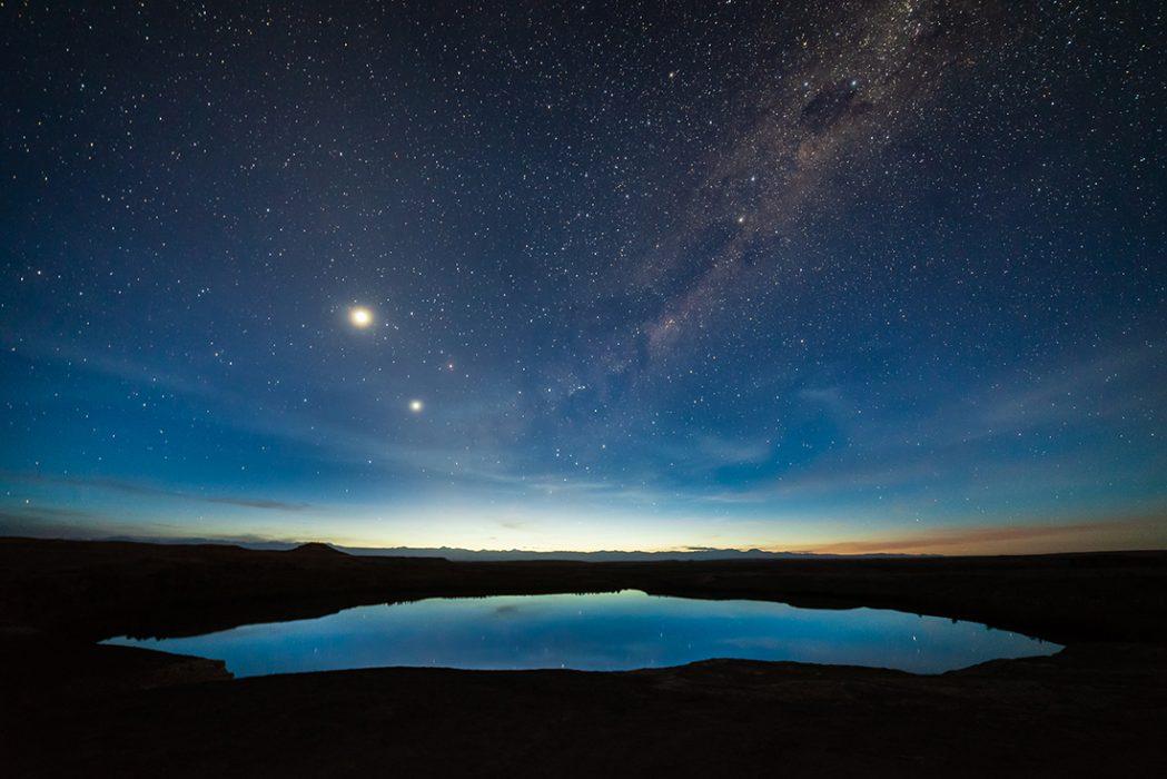 """""""Despertar del universo""""Mención Honrosa.""""Laguna Inca Coya mostrando la conjunción entre Venus y Júpiter, la constelación de Escorpio casi asomándose al centro de la Vía Láctea y en el amanecer astronómico"""". Chiu Chiu, Región de Antofagasta.Autor: Miguel Nuñez; Calama.Premio: Binocular Celestron Upclose G2 7x35"""